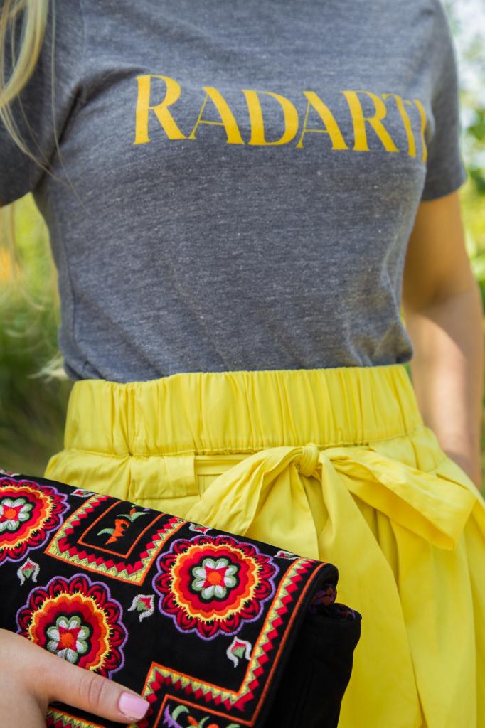 antik batik clutch,blue and yellow outfit,antik batik badra clutch,alaia booties,logo trend,alaia shoes,radarte t-shirt,ray ban mirror aviators,ray ban mirror aviators,yellow midi skirt,rodarte t-shirt