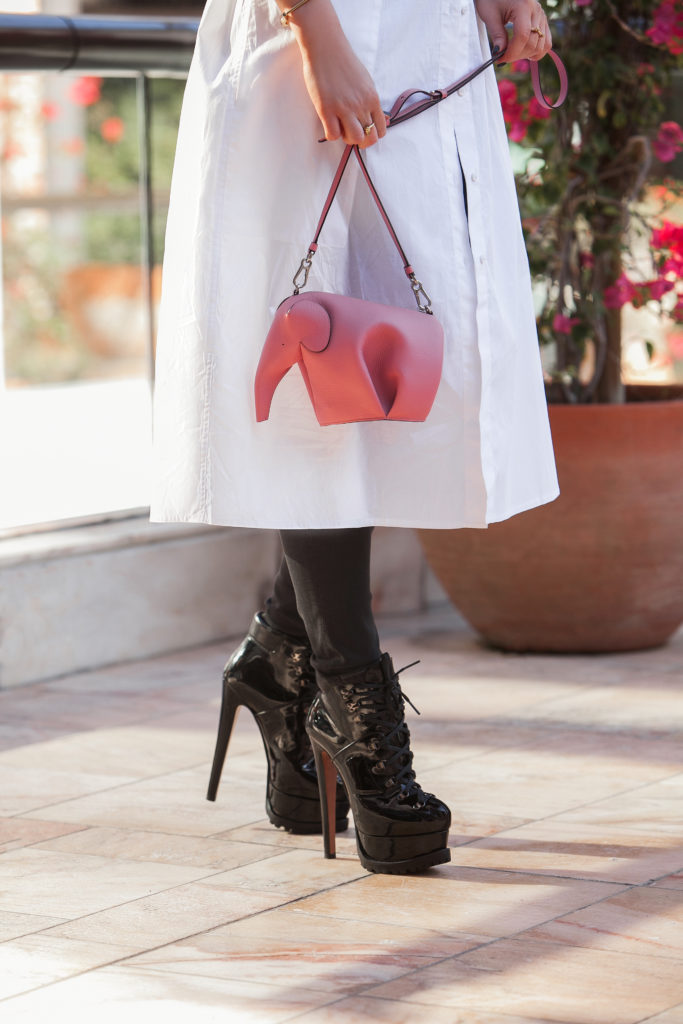 Loewe elephant,pop of color oufit,loewe pink elephant,how to wear button-down shirt,alaia lace-up boots,Loewe elephante bag,alaia biker boots,how to wear long white shirt,AG Jeans,AG Jeans skinny ankle jeans,White oversized shirt,Chanel choker,ryan storer outfit,Alaïa shoes,miansai