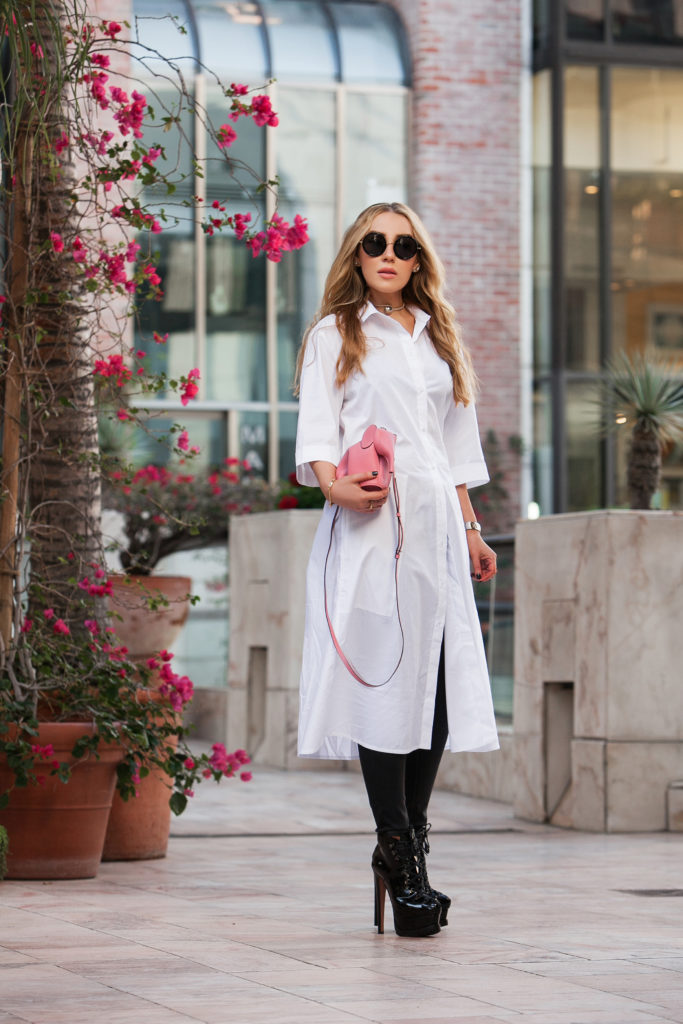 Loewe elephant,pop of color oufit,loewe pink elephant,how to wear button-down shirt,alaia lace-up boots,Loewe elephante bag,alaia biker boots,how to wear long white shirt,AG Jeans,AG Jeans skinny ankle jeans,White oversized shirt,Chanel choker,,ryan storer outfit,Alaïa shoes